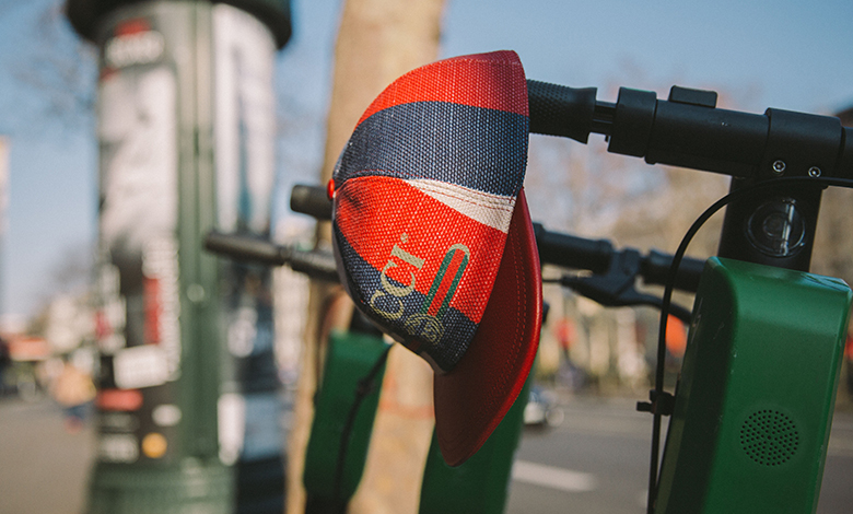 A red, white and blue stripe Gucci logo cap hanging on a pair of bike handles