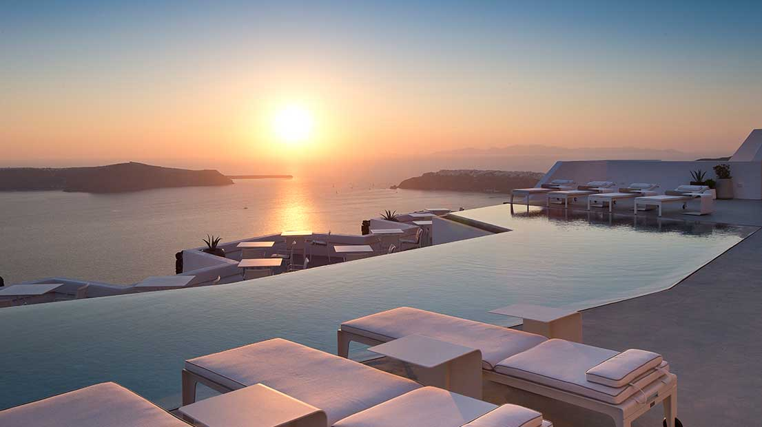 The inifnity pool with views over the Aegean sea at sunset at the Grace Hotel in Santorini