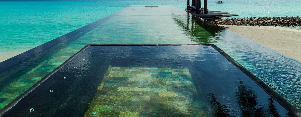 The pool within the sea withi views across the ocean and palm trees in the foreground at the One&Only Reethi Rah hotel in the Maldives