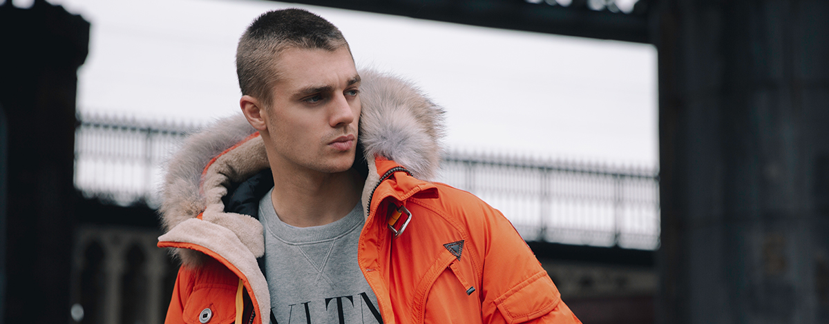 Model wearing a Parajumpers musher orange parka and Valentino VLTN logo sweatshirt in grey