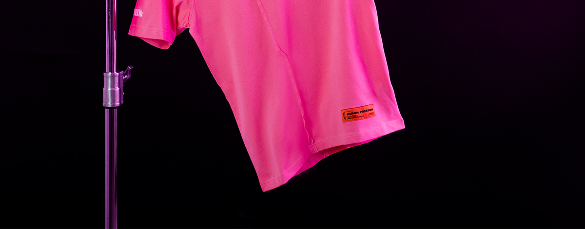 A still life image of the FLANNELS X Heron Preston exclusive pink T-shirt with the designer's signature cyrillic text, orange label and an illustration of a ghost