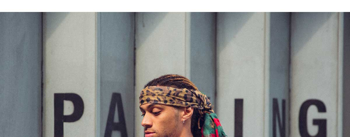 Bluey Robinson in an urban setting wearing a leopard print Gucci bandana and a white Valentino logo T-shirt