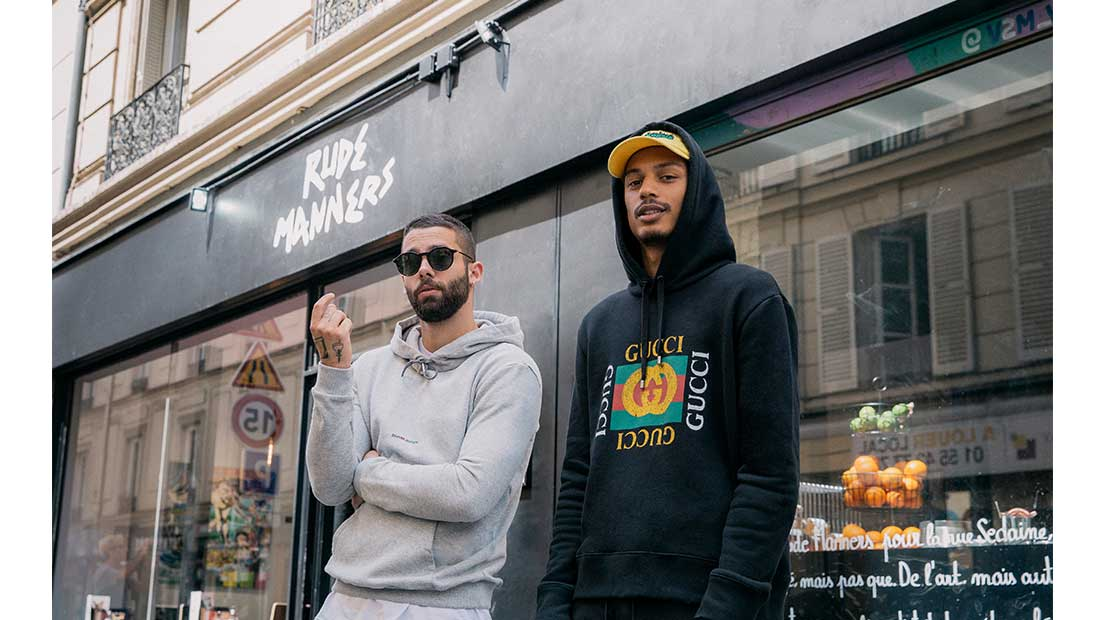 Ysham Avdulahi sat outside Rude Manners cafe in Paris wearing a Gucci Fake logo sweatshirt, Off-White jogging bottoms and Gucci logo trainers