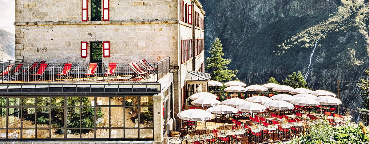 The rustic stone hotel Terminal Neige Refuge in the mountains of chamonix, surrounded by terraces with red deck chairs and umbrellas and the dramatic sheer face on the mountain in the background