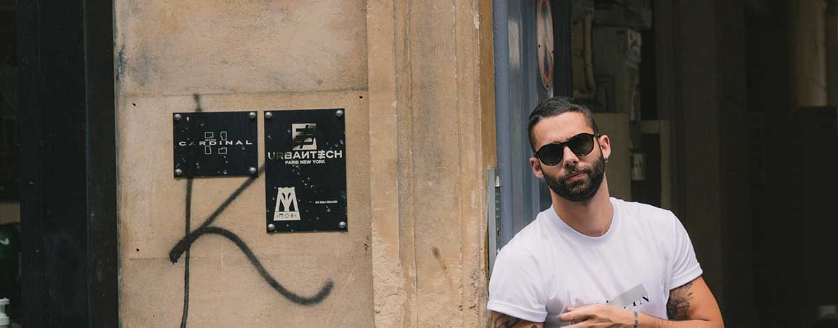 Jimmy Launay the founder of Rude Manners on the street in Paris wearing a Lanvin logo T-shirt, Givenchy biker jeans and Givenchy sunglasses