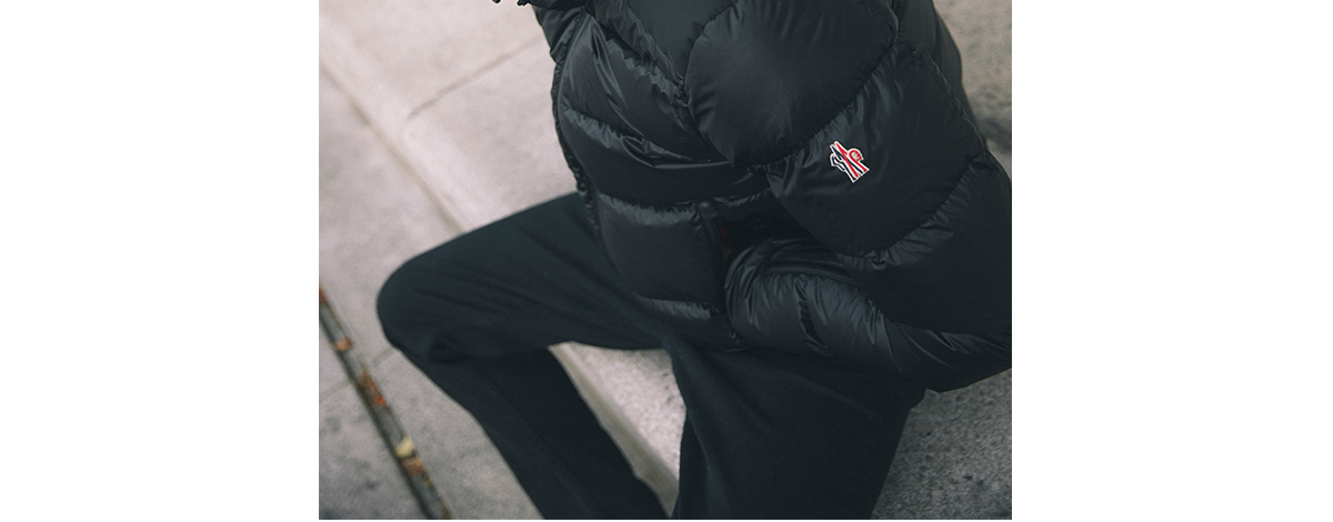 Model wearing a black Moncler down puffer jacket