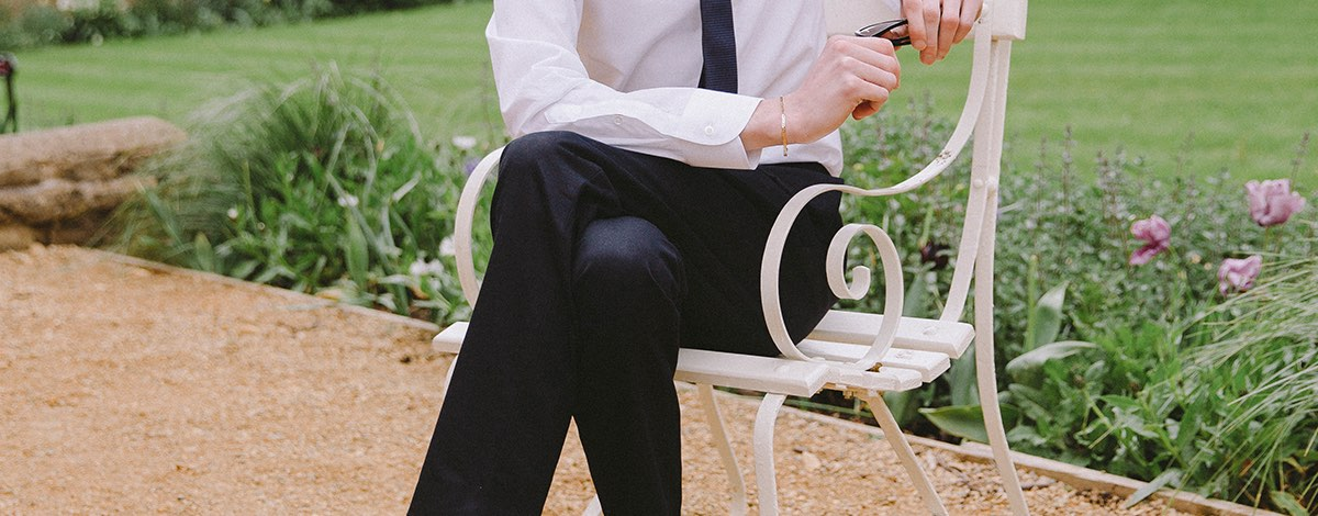 Danny Lomas sat on a white metal garden chair in an English country garden wearing a pair of Gucci trousers, a white Gucci shirt with an emboridered collar and a navy Gucci tie