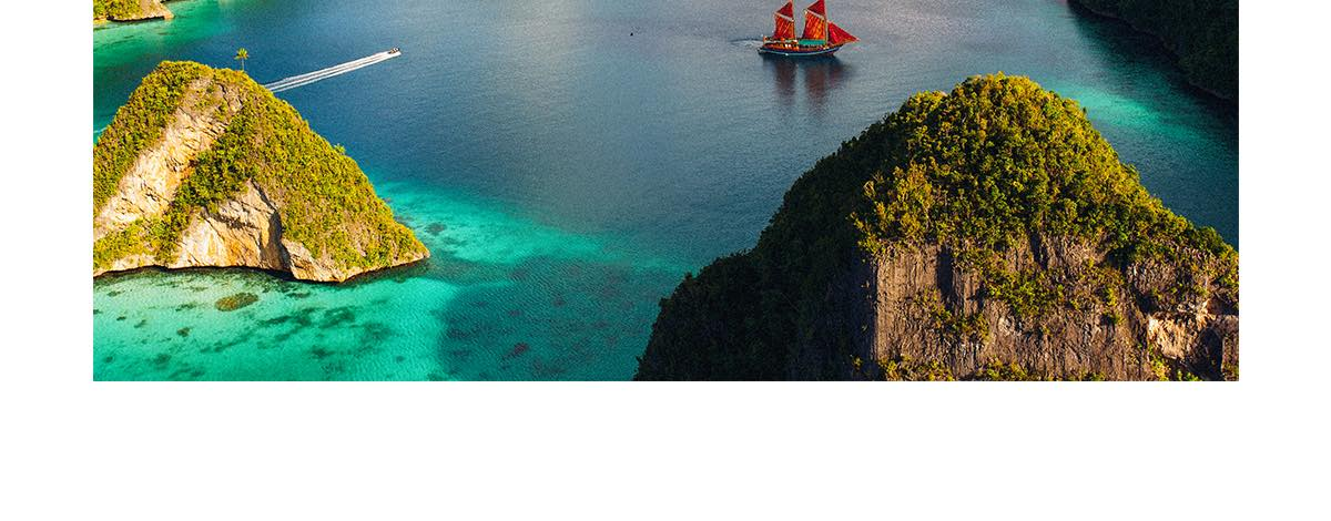A view of small islands in the sea in Indonesia's Raja Ampat with traditional phinisi boats sailing on the water
