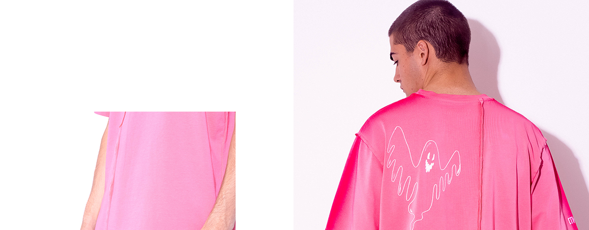 A male model wearing the FLANNELS X Heron Preston exclusive pink T-shirt featuring a ghost illustration on the front and back