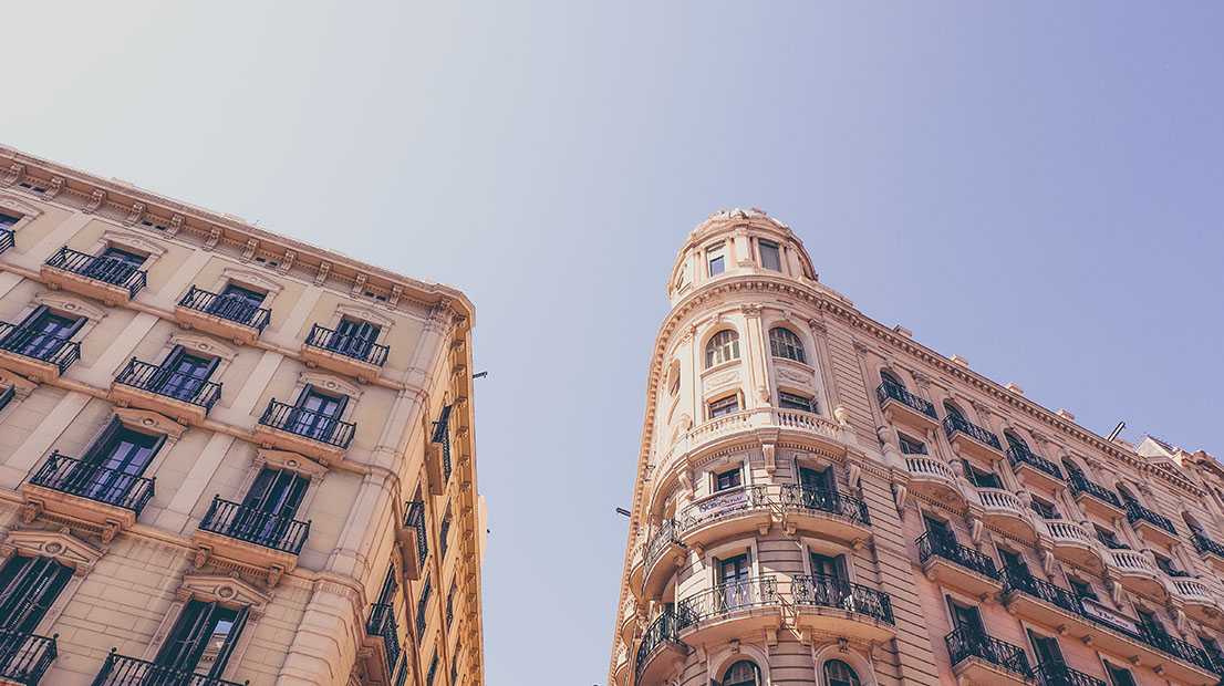 The exterior of an old multi-storey apartment block with ornate windows and balconies in the Barcelona sunshine