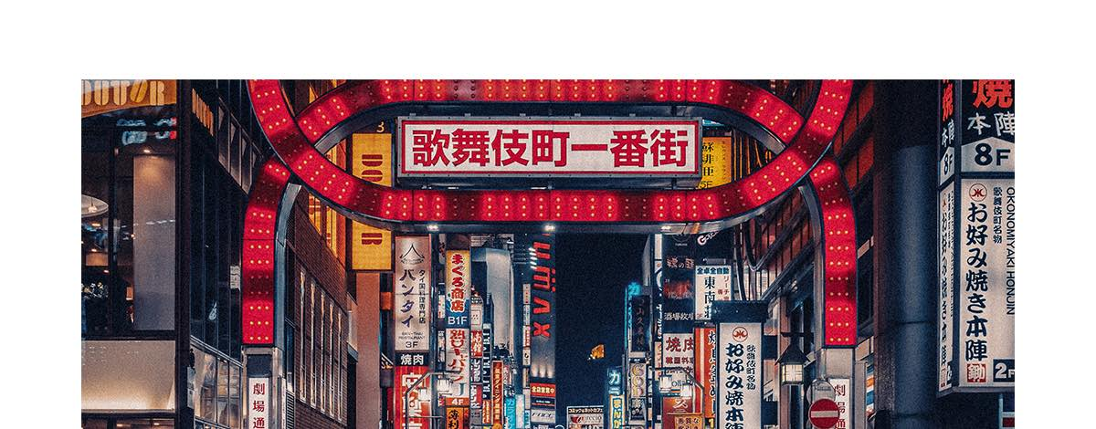 A busy street scene in Tokyo, Japan, filled with neon lights, crowds of people and a red taxi