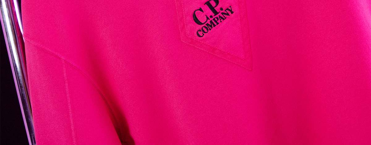 A close-up still life of the black C.P Company embroidered logo on the front of the FLANNELS X C.P. Company exclusive pink sweatshirt