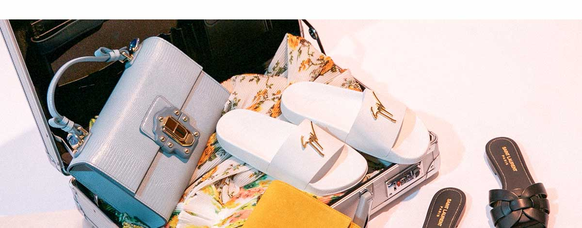 Suitcase packed with floral Zimmermann cut-out dress, yellow Saint Laurent Kate bag, Giuseppe Zanotti white and gold sliders, Saint Laurent sandals and Tom Ford shades