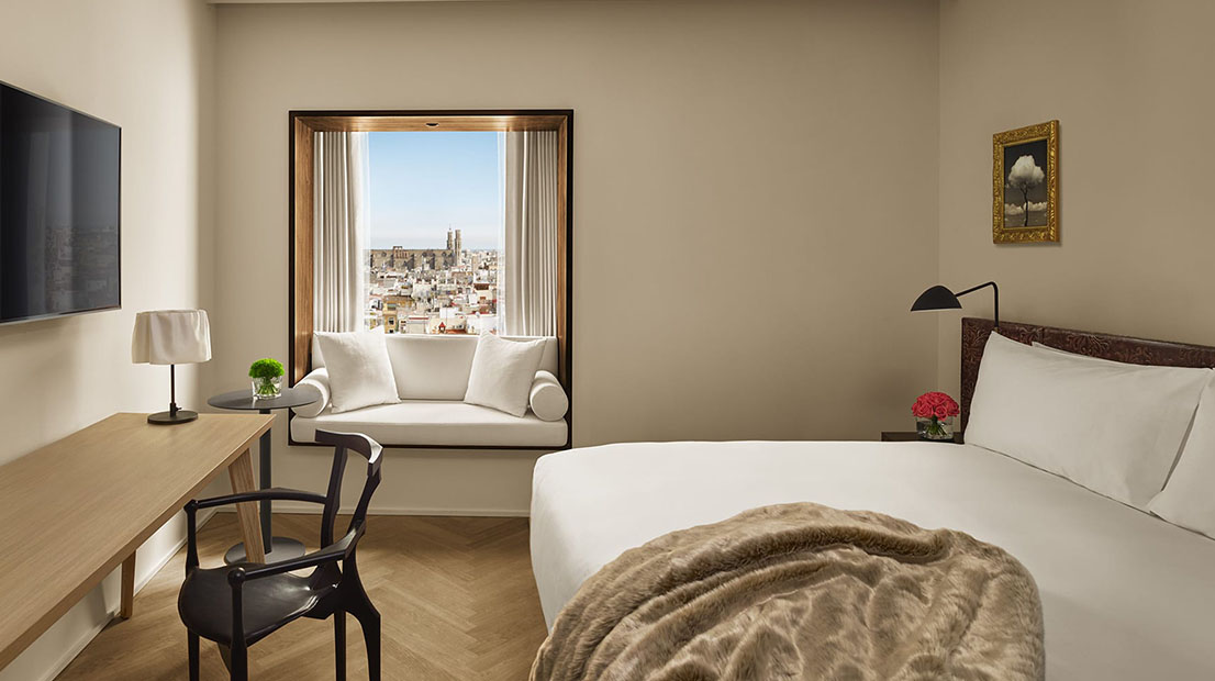 The stylish interior of a room at the Barcelona Edition with a white linen covered bed and views of the city