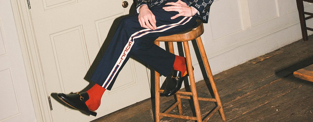 Danny Lomas sat on a stool wearing a white Gucci shirt with a Gucci all-over ambroidered GG blazer in navy and white, navy Gucci track pants with a white Gucci stripe and logo, red socks and backless black leather Gucci mules