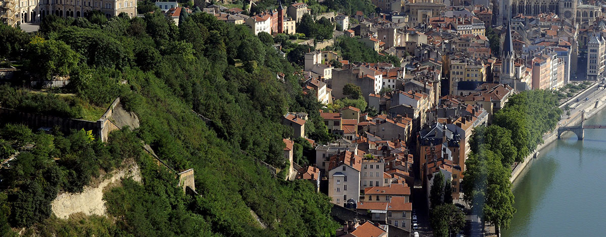 A view of the French city of Lyon with churches and buildings on a hillside running down to the river