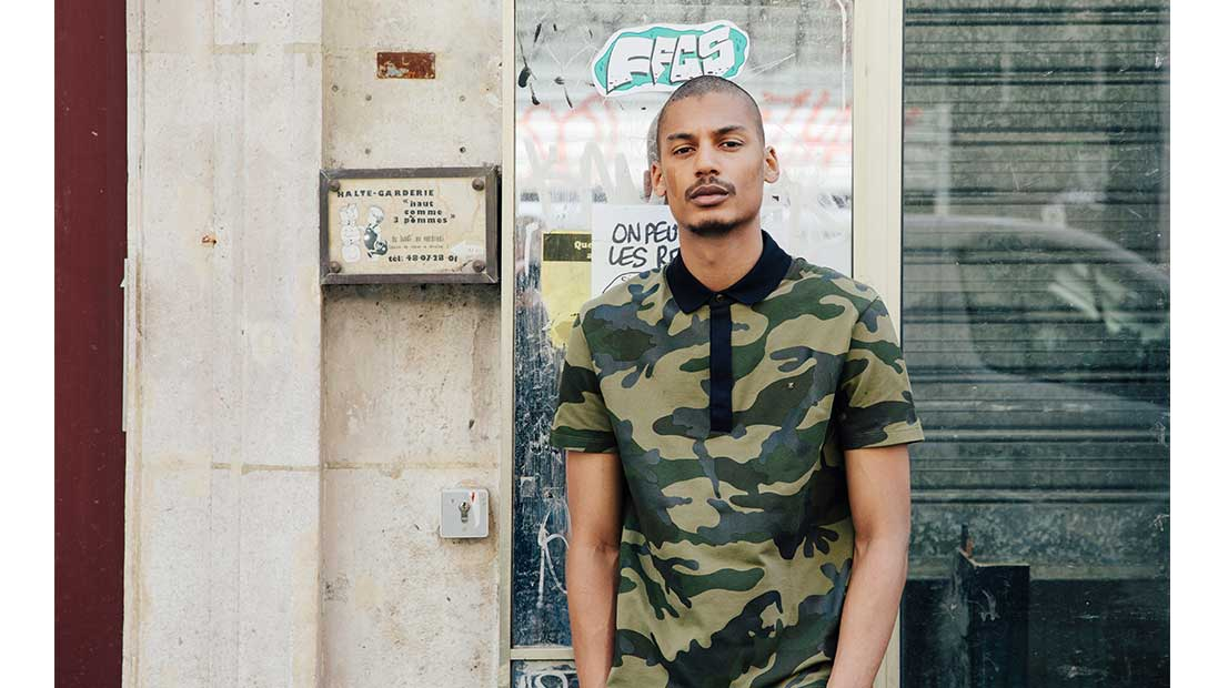 Ysham Avdulahi stood against a graffitied wall wearing a camouflage Valentino polo shirt and track pants