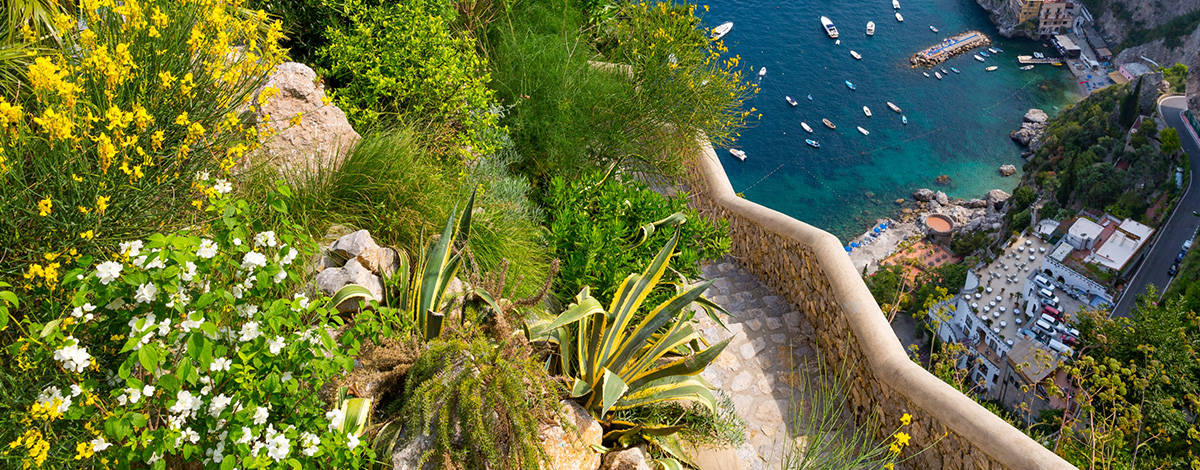 A birdseye view of the infinity pool at Hotel Monastero Santa Rosa on Italy's Amalfi Coast - it appears to jut out into thin air from the cliff, with a view of boats bobbing on the sea below