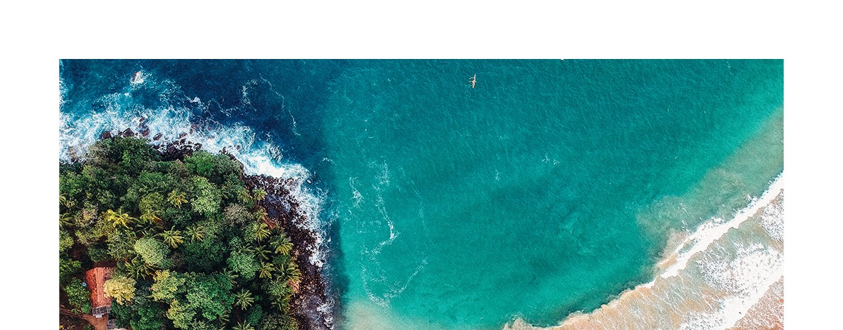 A birds-eye view of crystal clear blue waves lapping a sandy beach littered with small boats and bordered with tropical trees on the Sri Lankan coast