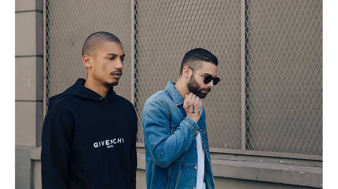 Ysham Avdulahi and Jimmy Launay walking in the street wearing a Givenchy logo hooded sweatshirt and denim biker jacket
