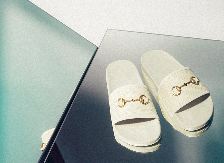 White Gucci Persuit sliders with gold horsebit