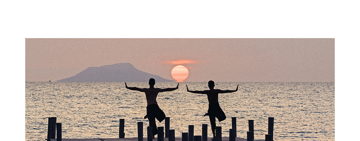 Two silhouettes of people practicing yoga at the end of a jetty stretching out to sea at sunset with another island on the horizon in Cambodia