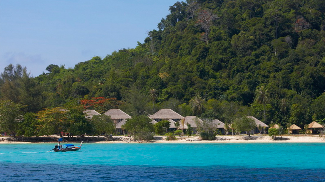 Beach huts, white sands, blue sea and jungle with a longtail boat on Koh Kradan Island, Thailand