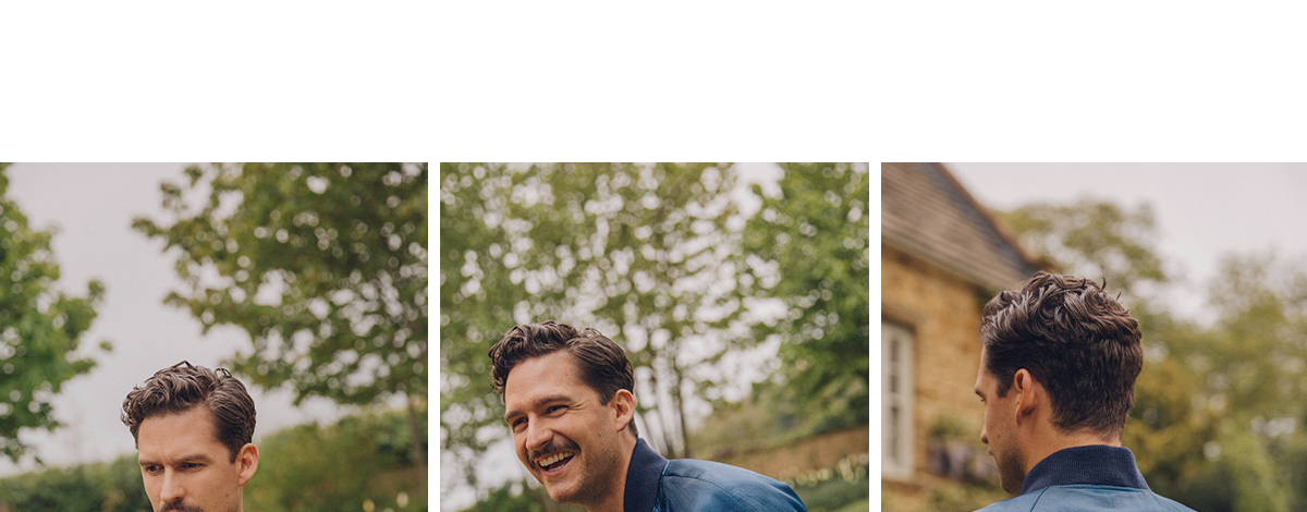 Actor Ben Aldridge in the grounds of an English coutnry house wearing a blue silk Gucci NY Yankees bomber jacket