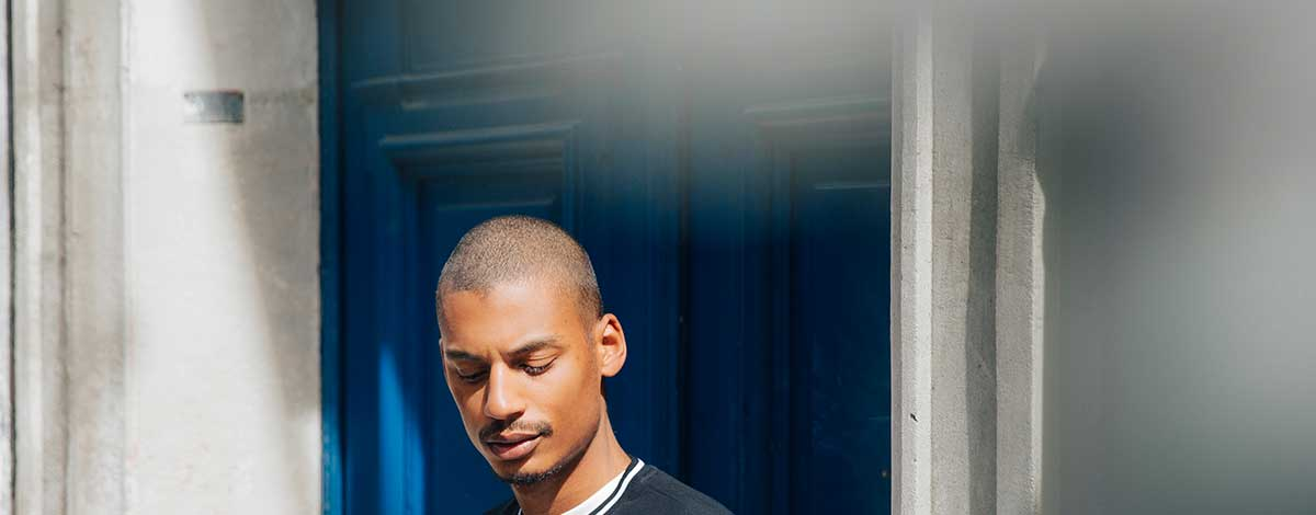 Ysham Avdulahi stood in front of a blue door in Paris wearing a Givenchy logo pre-fall sweatshirt