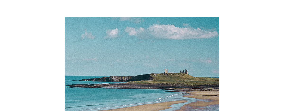 A view of the sea and Dunstanburgh Castle over Embleton Bay, Northumberland
