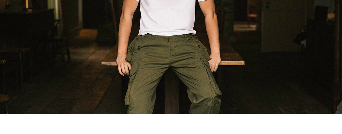 Actor Ben Aldridge sat on a table in an English country house, looking straight into the camera, wearing a pair of khaki green cargo trousers and a white Valentino T-shirt with a red VLTN logo on the front