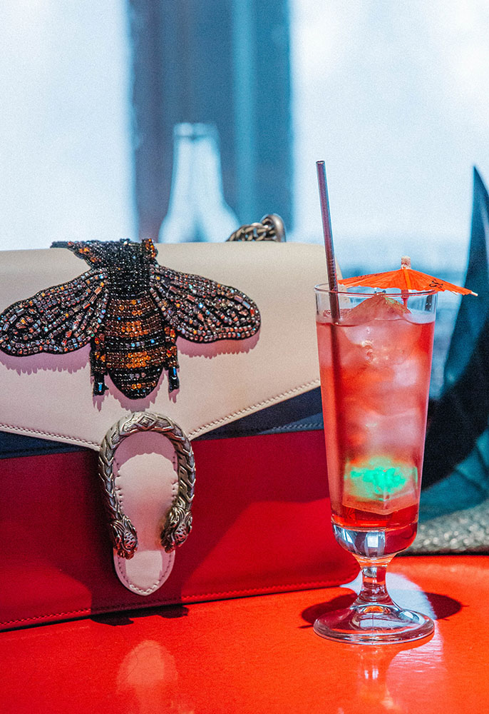 A Tick Tack cocktail at Sexy Fish in Mayfair on the bar with an embroidered Gucci Dionysus handbag