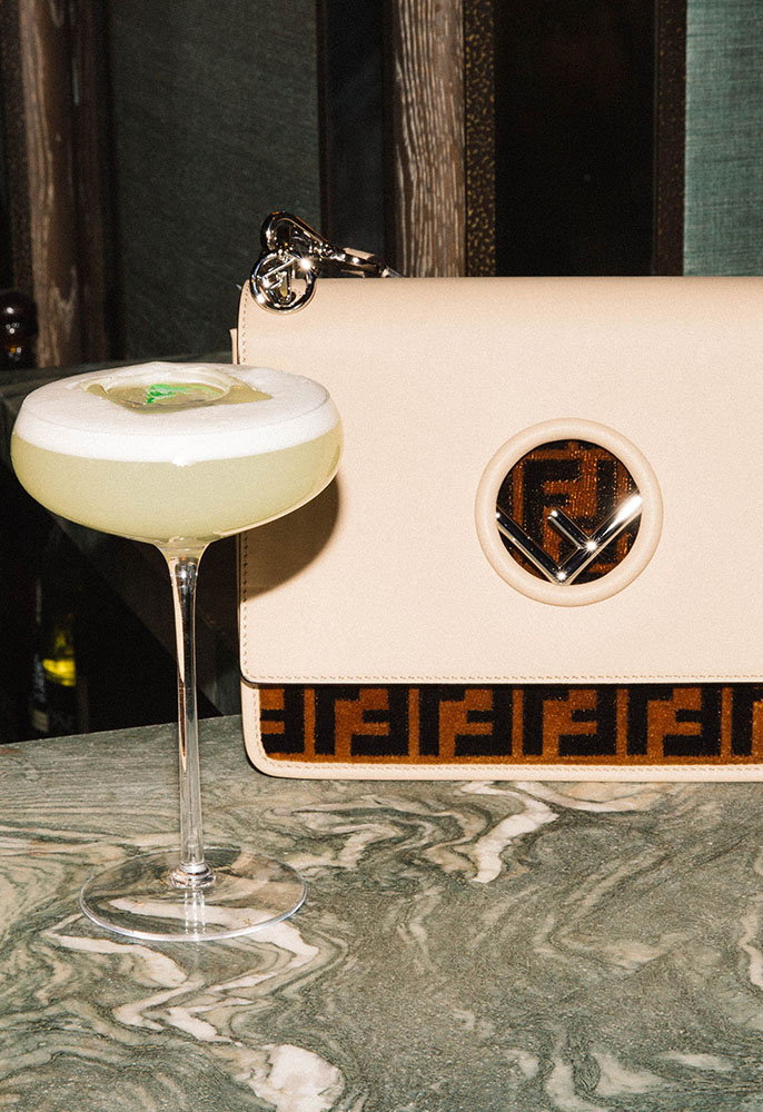 A Siren's Call cocktail on the bar at Sexy Fish in Mayfair with a Fendi Kan I Bag