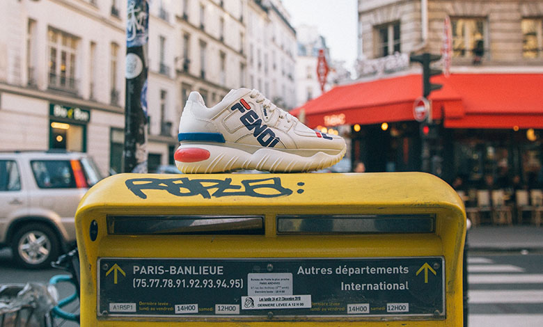 A Fendi X Fila logo trainer resting on top of a yellow post box in Paris with a cafe behind