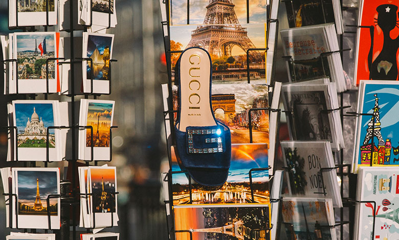 A Gucci blue velvet and crustal embellished mule hanging amongst postcards of typical Parisian scenes