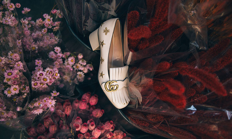 A pair of Gucci bee embroidered mules amongst pink and purple flowers