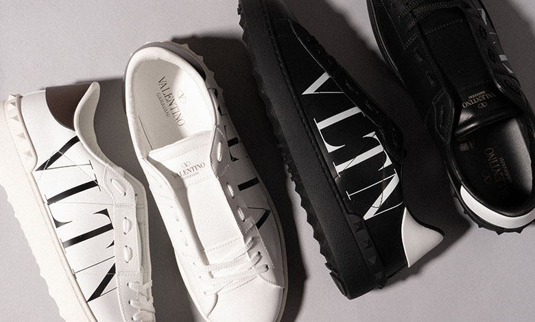 Two pairs of Valentino open band low-top trainers in white and black leather with the VLTN logo on the side panel