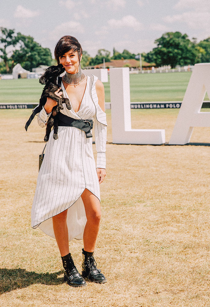 Model Eliza Cummings with her dog at the FLANNELS polo summer party wearing a Self Portrait dress