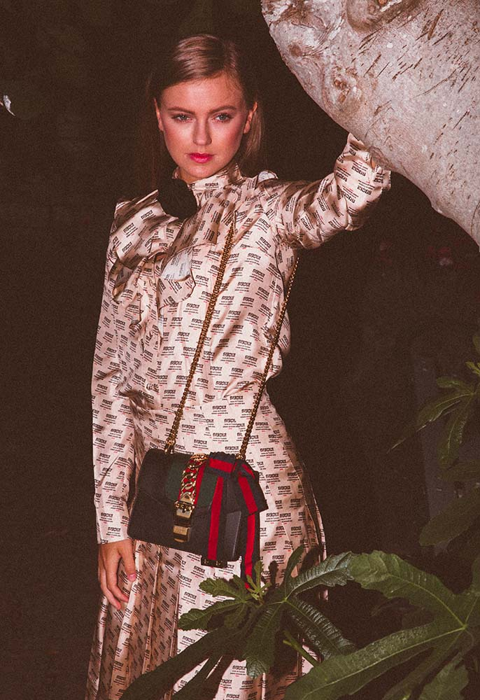 Model wearing a Gucci stamp print silk shirt and dress and a Gucci Sylvie mini bag