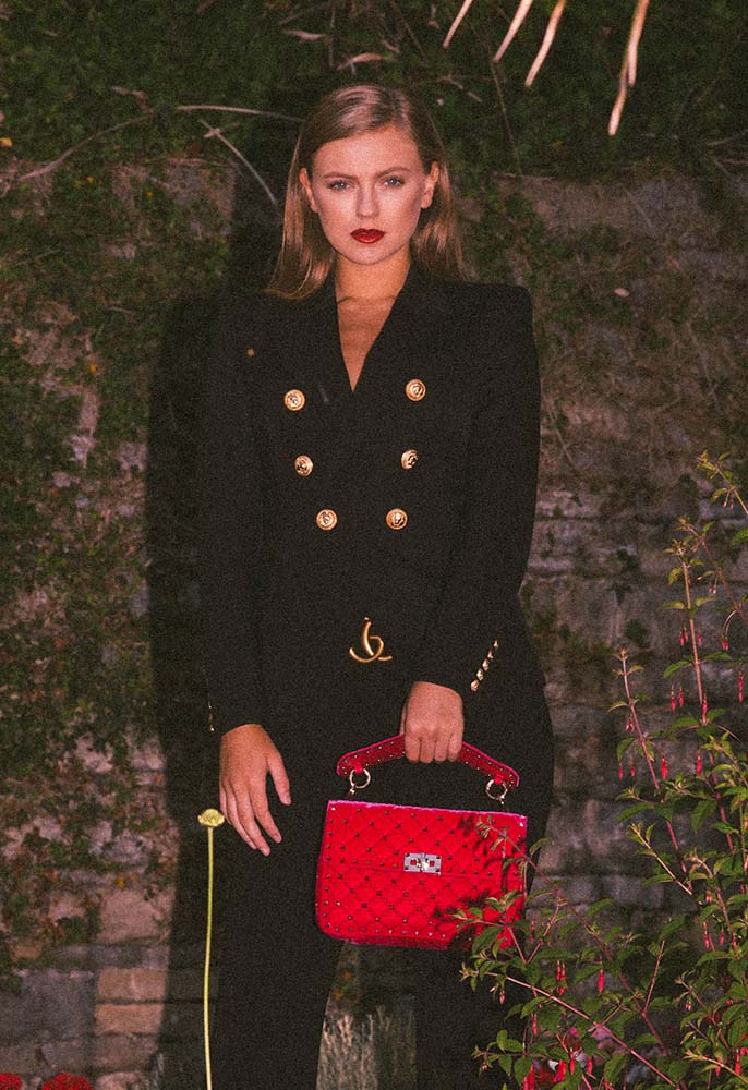 Model wearing Gucci double G trousers, a Balmain double breasted blazer and hot pink velvet Valentino Rockstud bag