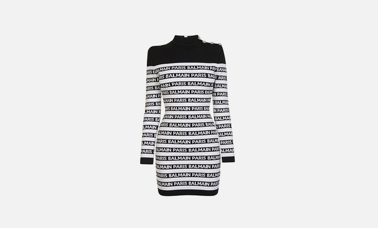 A black and white striped Balmain mini bandage dress with long sleeves and Balmain logos written in type and silver button epaulettes