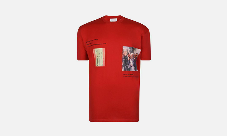 A red Burberry T-shirt with graphics and typography including a train ticket and words from Shakespeare's Richard II printed on it