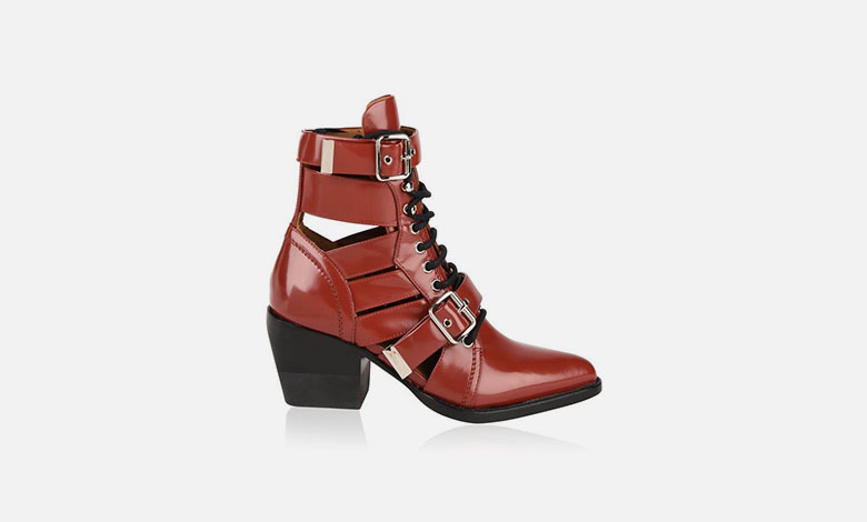 Red leather Chloe Rylee boots with cut outs, a pointed toe, black laces and two straps with silver buckles