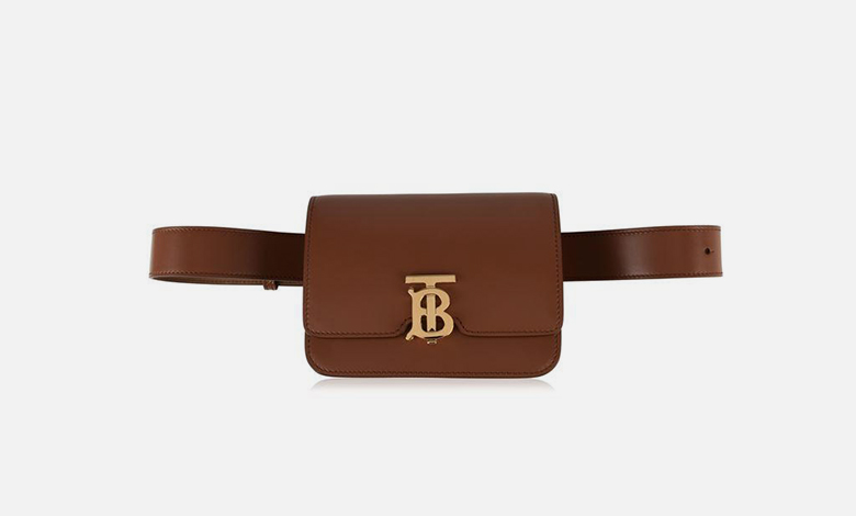 A tan leather Burberry belt bag with a metal TB logo clasp and buckle fastening
