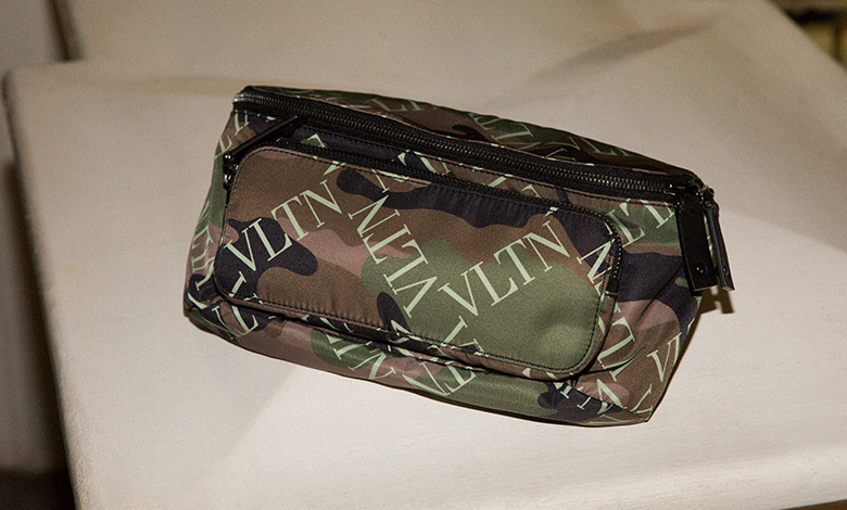 A Valentino bum bag in a camouflage print with a utility zip front pocket and heavy metal buckle closure