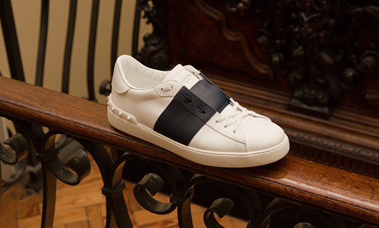A white Valentino Open Band trainer with white studs and laces and a navy blue centre panel stripe