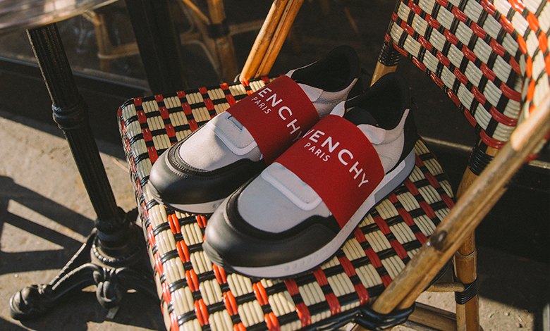 A pair of Givenchy active running trainers sitting on a wicker chair at a Paris cafe