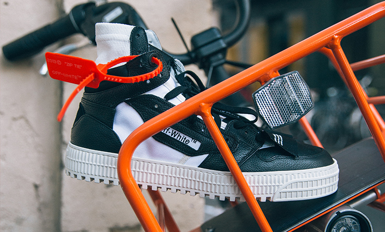 A pair of Off-White black and white high top trainers sitting in a bike basket in Paris