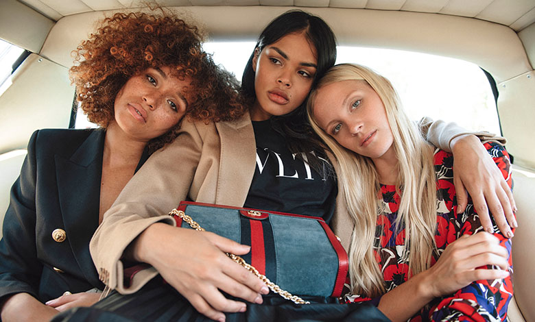 Three female models in the back seat of a vintage car wearing Balmain, Victoria Beckham, Valentino, Gucci and Marni