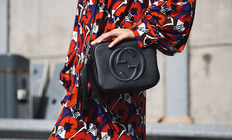 Model wearing a floral Marni dress and black leather Gucci Soho camera bag